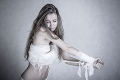 Pretty young woman with a bandage dressings on her body. Over grey background royalty free stock image