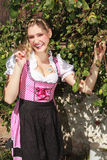 Pretty young woman in a Bavarian dirndl. Pretty young blond woman in a Bavarian dirndl standing outdoors in the sunshine in front of green leaves laughing and royalty free stock photos