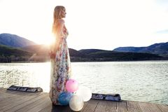 Pretty young woman in beautiful dress with a lot of colorful balloons on the pier. Royalty Free Stock Photo