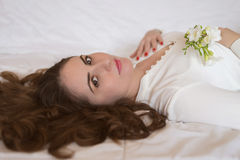 Pretty young woman, with beautiful long hair lying on the bed. Holding a freesia flower Stock Images