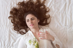 Pretty young woman, with beautiful long hair lying on the bed. Holding a freesia flower Royalty Free Stock Photos