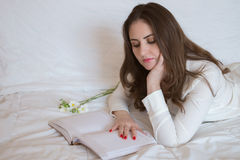 Pretty young woman, with beautiful long hair lying on the bed. Reading a book Royalty Free Stock Photography