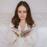Pretty young woman, with beautiful long hair lying on the bed. Reading a book Stock Photography