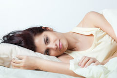 Pretty young woman in bed Stock Photography