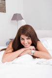 Pretty young woman on the bed smiling Royalty Free Stock Photo