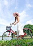 Pretty and young woman with bicycle. At outdoor lake garden Royalty Free Stock Image