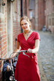 Pretty young woman with bicycle. Young blond woman in red dress standing on a street with old bicycle Stock Image