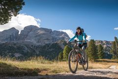 Pretty young woman on bicycle in italien dolomites,  south tyrol, platzwiese Stock Photo