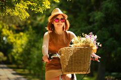 Pretty young woman with bicycle in the park Stock Image