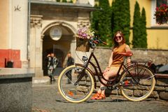 Pretty young woman with bicycle in the park Royalty Free Stock Image