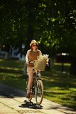 Pretty young woman with bicycle in the park Stock Photo