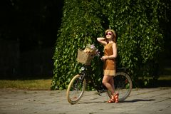 Pretty young woman with bicycle in the park royalty free stock photography