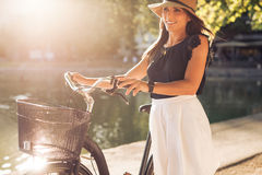 Pretty young woman with a bicycle in park Stock Photo