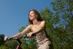 Pretty young woman with bicycle in a park smiling Royalty Free Stock Images