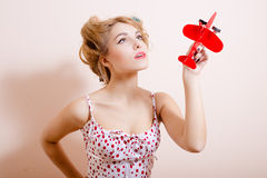 Pretty young woman in big curlers holding red toy Stock Photos