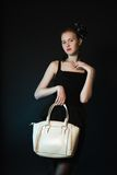 Pretty  young woman with big yellow bag standing posing Royalty Free Stock Photos