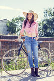 Pretty young woman on bike in a country road. Pretty young woman with hat on bike in a country road Stock Photography