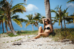 Pretty young woman in bikini is relax on a tropical beach under palm tree Royalty Free Stock Images