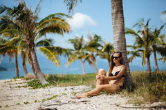 Pretty young woman in bikini is relax on a tropical beach under palm tree Stock Photography
