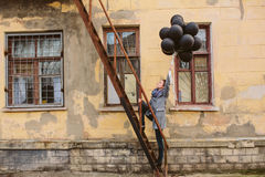 Pretty young woman with black balloons Stock Photography