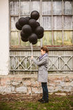 Pretty young woman with black balloons Stock Images
