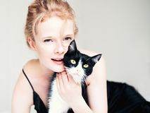 Pretty young woman with black cat in blanket. In white bedroom stock photos