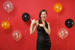 Pretty young woman in black dress celebrating blinking, pointing thumbs aside on bright red background air balloons. St. Valentine`s Women`s Day, Happy New stock photos