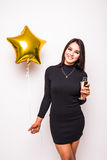 Pretty young woman in black dress with gold star shaped balloon smiling and drinking champagne Stock Photos