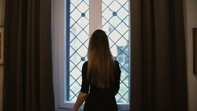 Pretty young woman in a black dress is pacing through the room, coming closer to the window. The girl opening window. Pretty young woman in a black dress is stock video footage