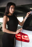 Pretty young woman in black dress standing near her car Stock Photography