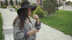 Pretty young woman in black hat and glasses using smartphone in city park. HD stock video footage
