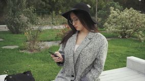 Pretty young woman in black hat and glasses using smartphone in city park. HD stock footage