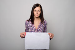 Pretty young woman blank banner. Pretty young woman holding a blank banner Royalty Free Stock Photos