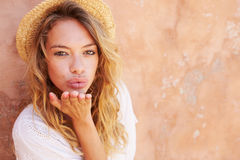 Pretty Young Woman Blowing Kiss Towards Camera Royalty Free Stock Images