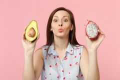 Pretty young woman blowing sending air kiss hold fresh ripe green avocado, pitahaya dragon fruit isolated on pink pastel. Background. People vivid lifestyle stock image