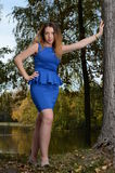 Pretty young woman in blue dress. In a park Stock Photos