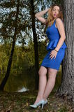 Pretty young woman in blue dress. In a park Stock Photography