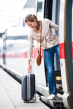 Pretty young woman boarding a train Royalty Free Stock Photo