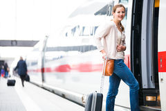 Pretty young woman boarding a train Stock Image