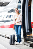 Pretty young woman boarding a train Stock Photo