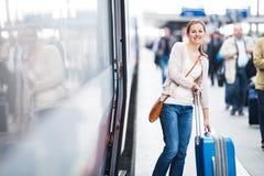 Pretty young woman boarding a train Stock Photo