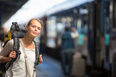 Pretty young woman boarding a train/having arrived to her destin. Ation, waiting for her friends to pick her up color toned image Royalty Free Stock Photos