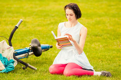 Pretty young woman with book and retro bicycle resting Royalty Free Stock Photos