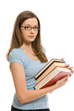 Pretty young woman with books. A pretty young woman, isolated against a white background, carries a stack of books Stock Photos