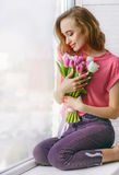 Pretty young woman with bouquet of tulips on window-sill. Pretty young woman in pink T-shirt with bouquet of tulips on window-sill stock photo