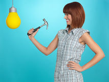 Pretty young woman breaking a light bulb Royalty Free Stock Photos