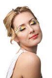 Pretty young woman with bright make-up. Pretty young woman portrait with bright yellow and blue make-up and long eyelashes royalty free stock photography