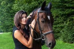 Pretty young woman and a brown horse Royalty Free Stock Photos
