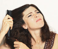 Pretty young woman with brush comb stuck in hair Royalty Free Stock Photography
