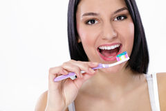 Pretty young woman brushing her teeth Royalty Free Stock Photography